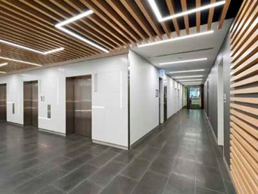 MAXI BEAM in SUPAFINISH laminate Tasmanian Oak lines the ceilings of the lift lobbies