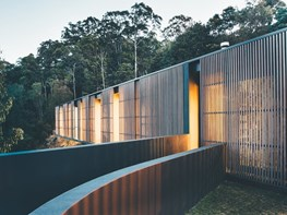 Glass home wrapped in sliding timber screens offers views and sun protection