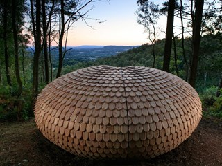 A pine-cone-like pavilion made from cedar shingles provides shelter for UK bushwalkers