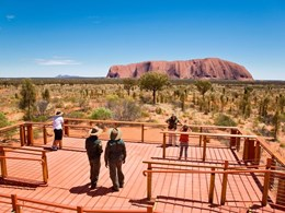 Visitors watch sunrise from Rocla concrete boardwalks in Uluru National Park, NT