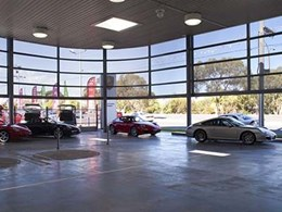 Perforated metal facade provides sun protection to showroom vehicles at Porsche Brighton