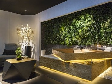 A 'green wall' and the hand carved oak bath provide an 'outside within' feeling. Photo courtesy Mitsui Designtec