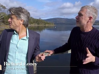 Two men in front of a lake