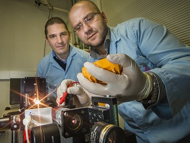 Associate professor Andrey Miroshnichenko (left) and doctor Mohsen Rahmani from ANU demonstrate how the nanomaterial can reflect or transmit light on demand with temperature control. Photography by Stuart Hay