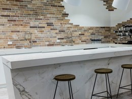 Imperfections add beauty to brick tiled wall in Studio Cafe kitchen